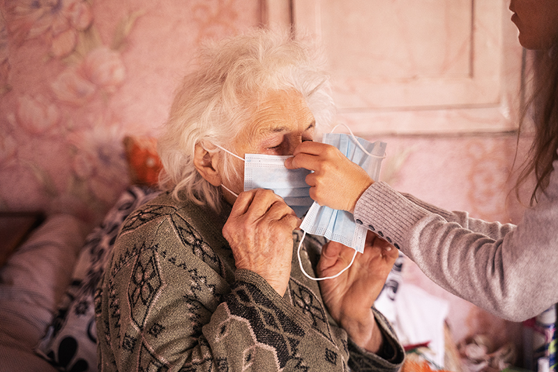 caregiver assisting senior woman with mask